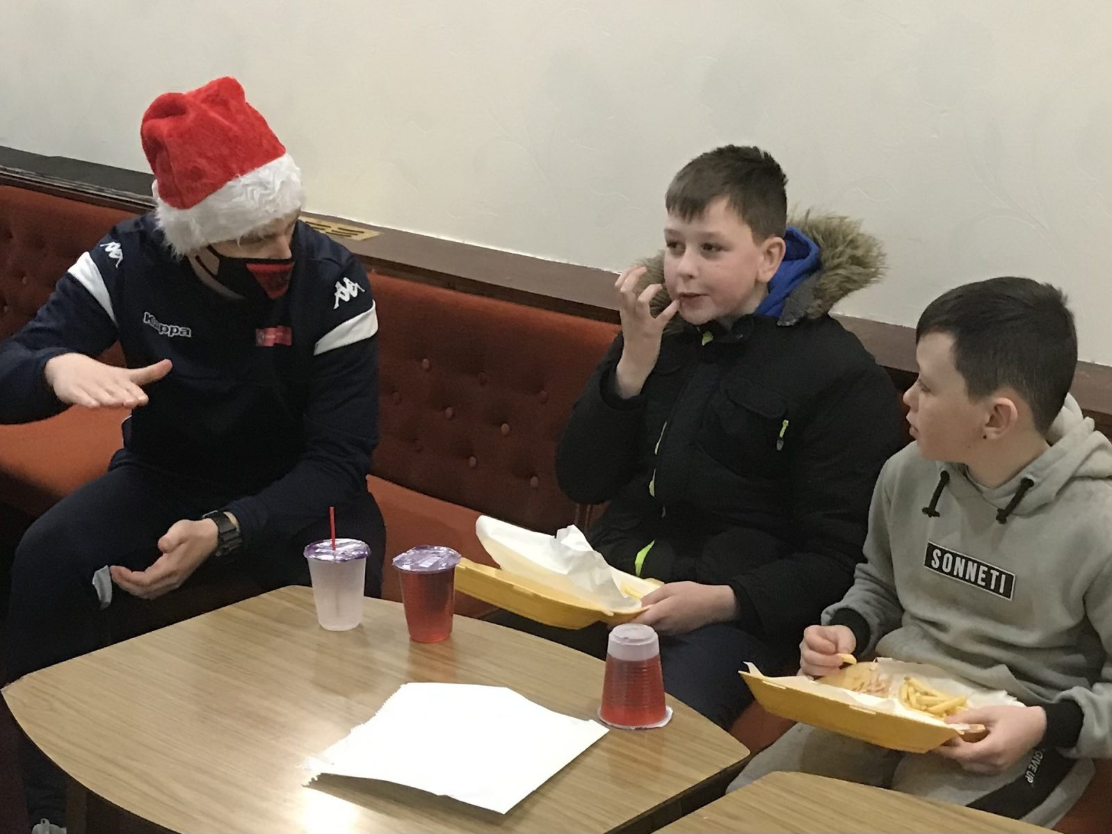 Community-meal-Steven-Rudd-explains-the-advantages-of-playing-3-5-2-to-two-young-diners