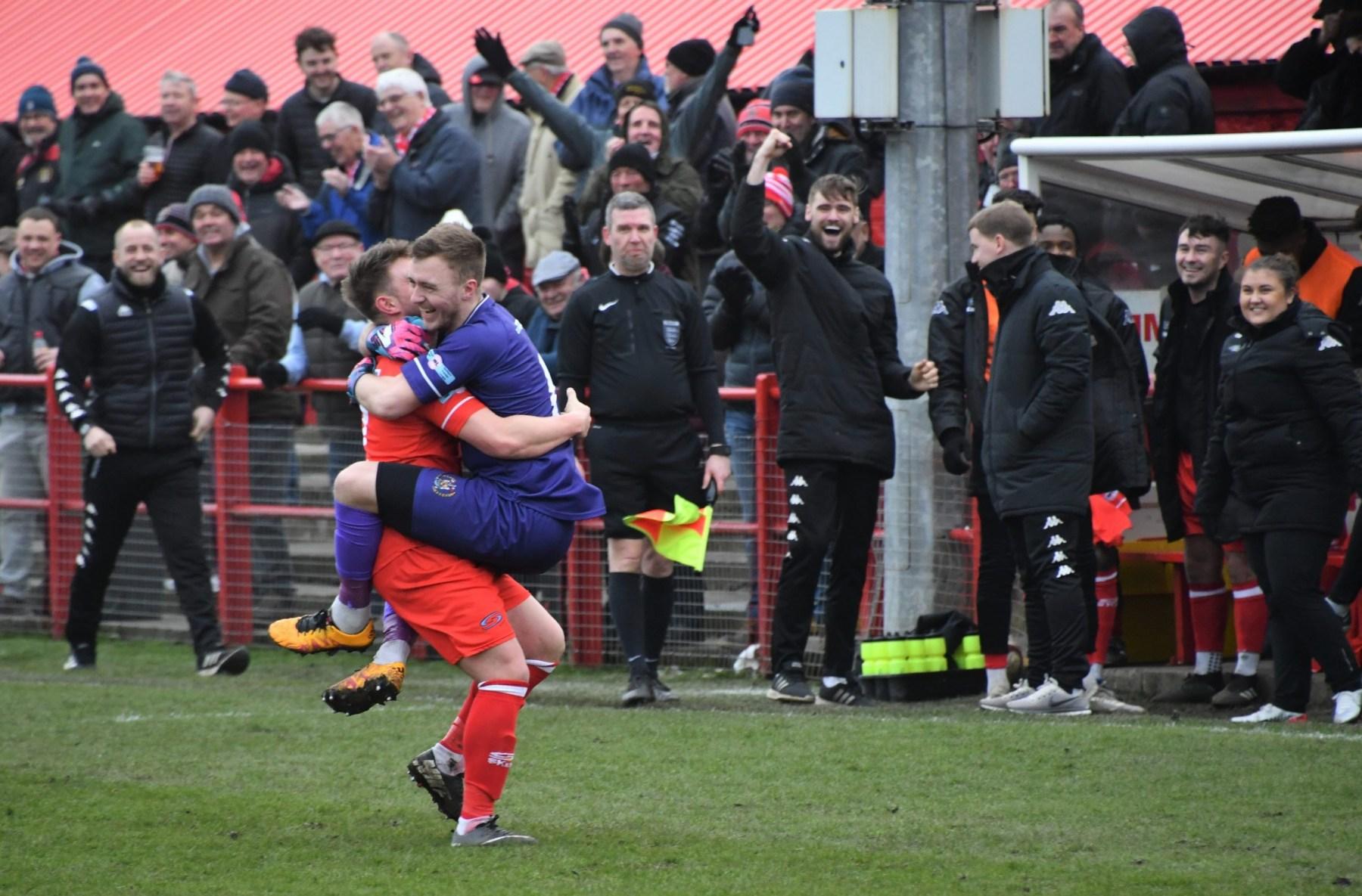 Dav-Symington-and-Jim-Atkinson-celebrate-the-Reds-1-0-lead-Ben-Challis-scaled